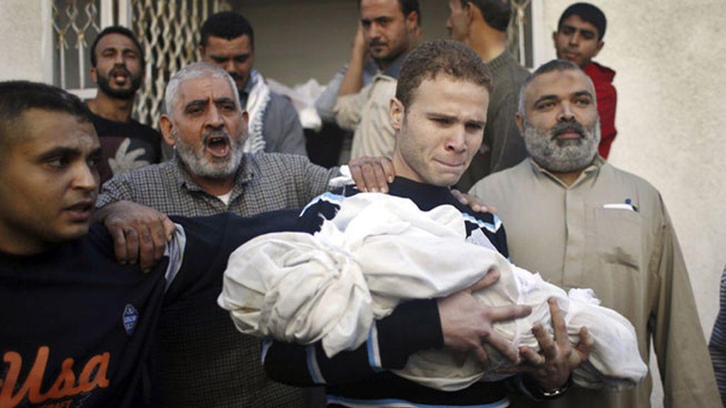 Un padre palestino lleva el cuerpo de su hijo muerto durante un ataque israelí en Gaza