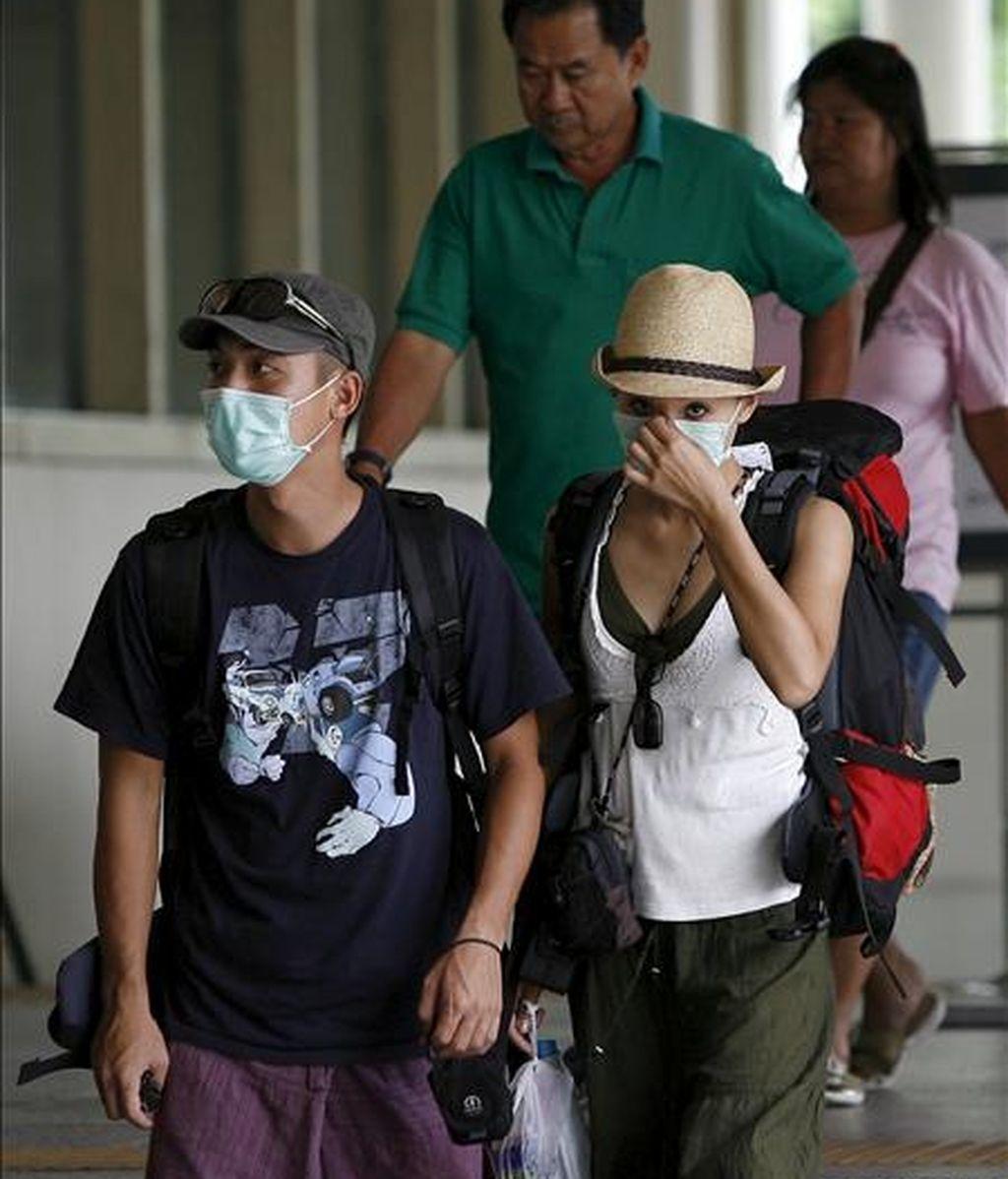 Dos turistas con máscaras caminan por la estación de tren de Bangkok, Tailandia. EFE/Archivo