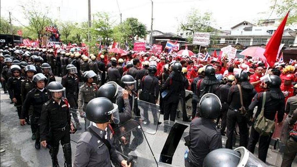 Policías antidisturbios toman posiciones ante un grupo de simpatizantes del ex primer ministro tailandés Thaksin Shinawatra vestidos de rojo en los alrededores de la residencia del presidente del consejo real, Prem Tisunalonda, en Bangkok (Tailandia) hoy miércoles 8 de abril. Varios miles de manifestantes iniciaron hoy una protesta en Bangkok para exigir la renuncia del Gobierno de Tailandia, al que acusan de antidemocrático. EFE/Narong Sangnak