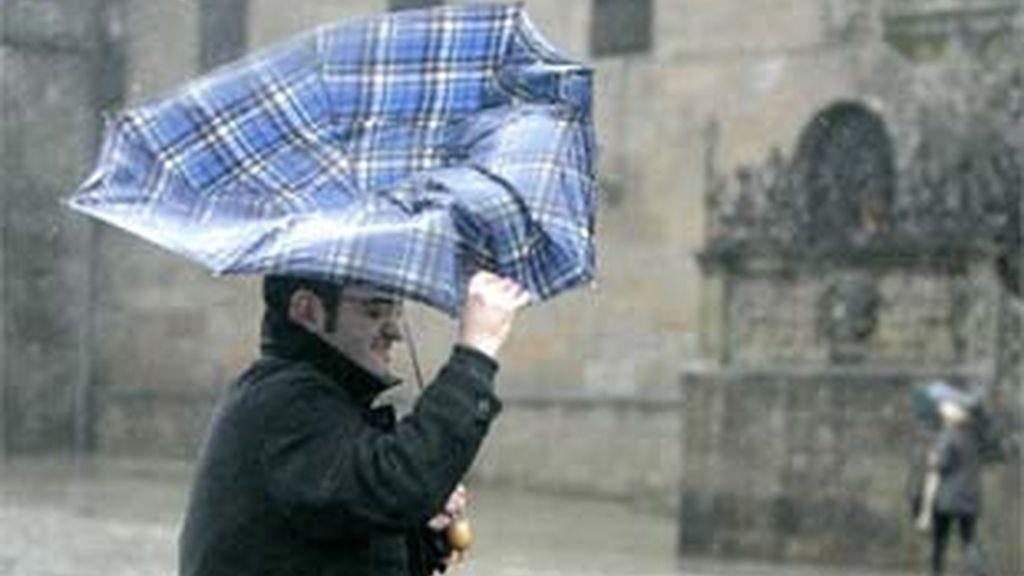 Una persona se resguarda de los fuertes vientos y la lluvia en Santiago de Compostela. Foto: EFE.