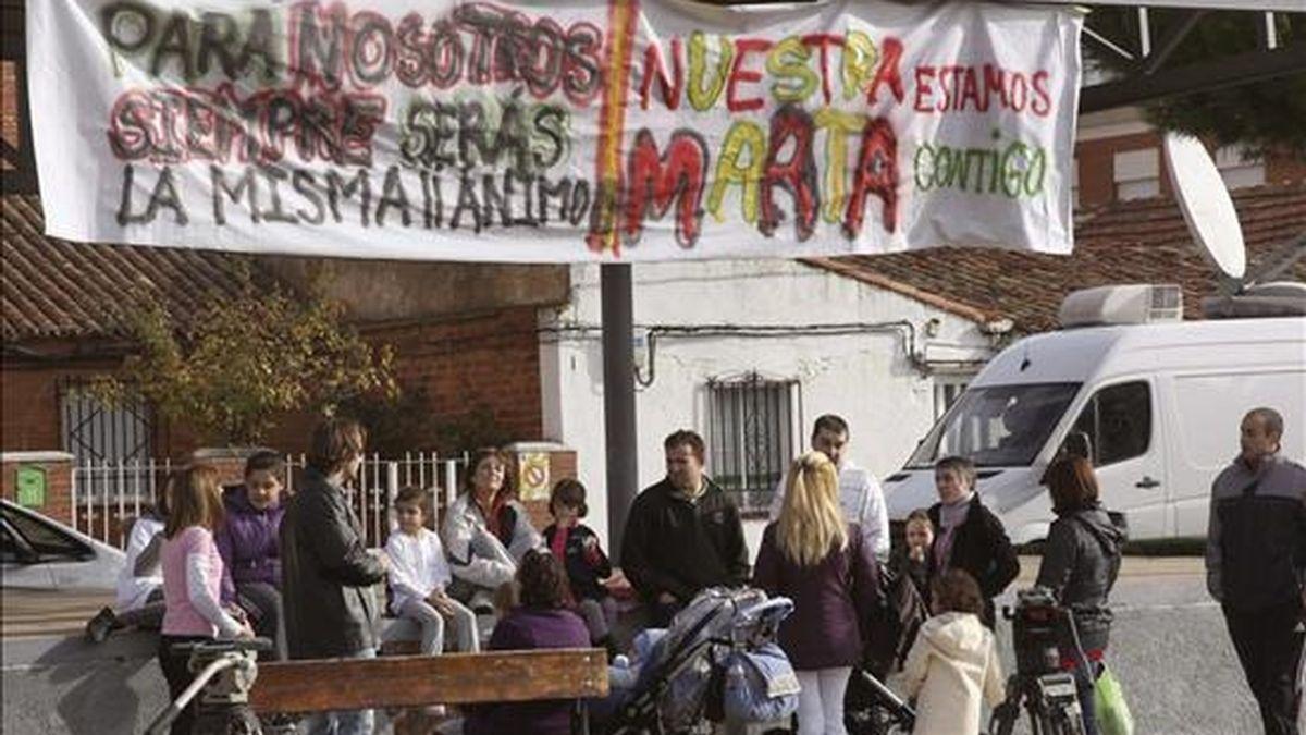 Varias personas junto a una pancarta de apoyo a la atleta Marta Domínguez esperan ante la vivienda de la deportista en Palencia. EFE
