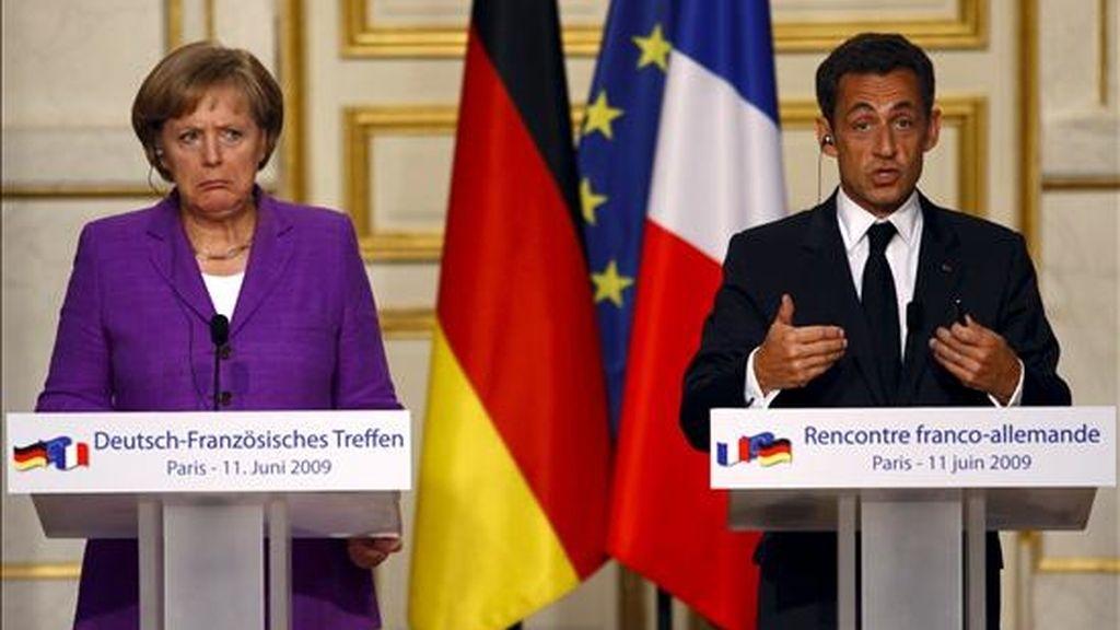 El presidente francés, Nicolás Sarkozy (d), y la canciller alemana, Ángela Merkel, hablan durante una rueda de prensa mantenida al término de su reunión en el Palacio del Elíseo en París (Francia). EFE
