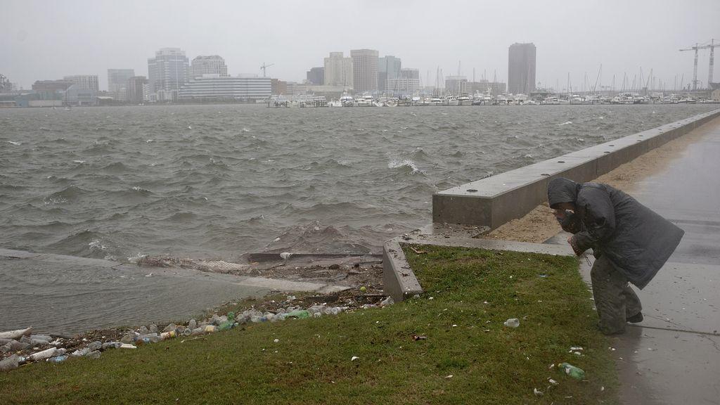 Una mujer se agacha para capear el huracán