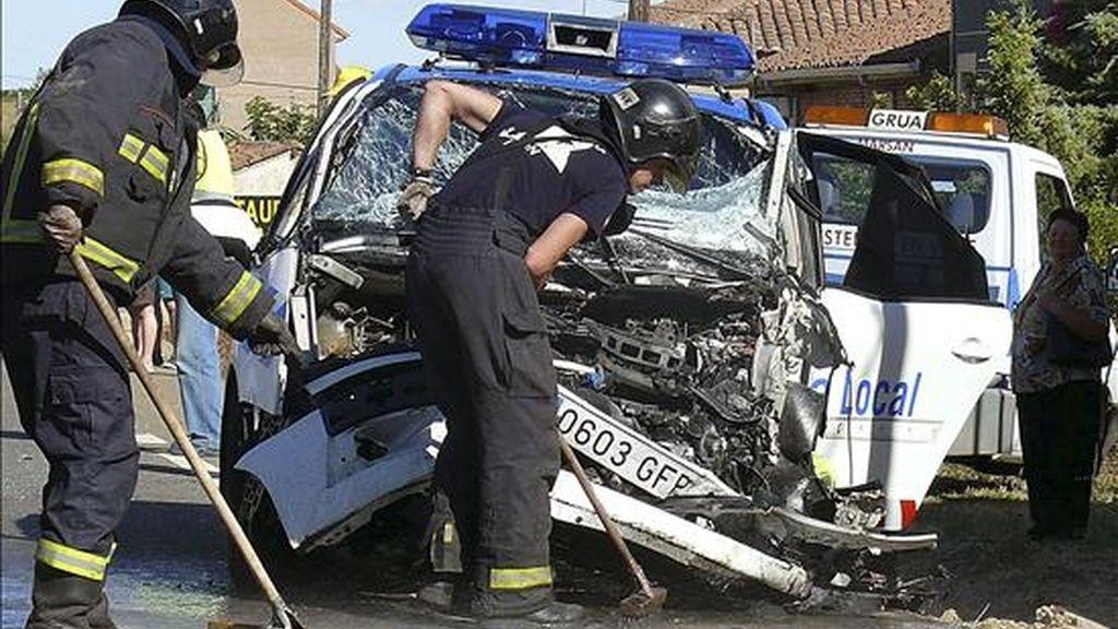Integrantes del cuerpo de bomberos en el lugar en el que un hombre ha fallecido hoy y otros dos, ambos policías locales, han resultado heridos en una colisión frontal registrada en la N-601 (León-Valladolid), a la altura de la localidad leonesa de Valdefresno, durante la persecución del supuesto autor de un robo. EFE