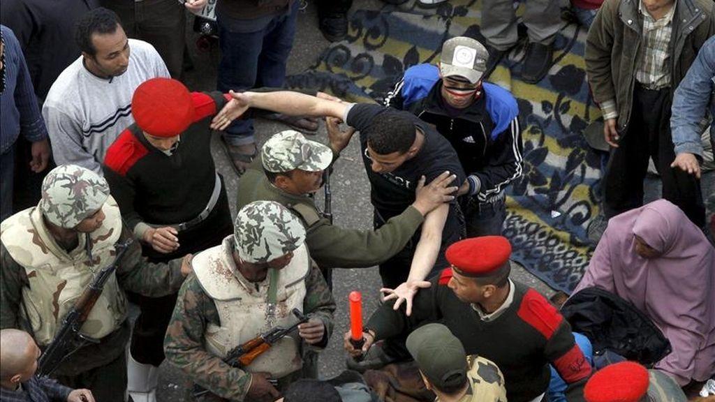 Soldados egipcios intentando frenar hoy a los manifestantes que insistían en no abandonar la plaza cairota Tahrir hasta que el Ejército anunciara un plazo determinado para cumplir con sus peticiones, la primera de ellas la anulación de la ley de Emergencia, vigente desde 1981. EFE