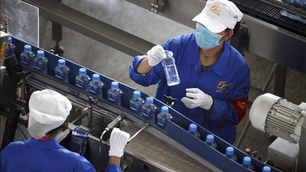 Trabajadores supervisan una línea del proceso de embotellamiento en China. EFE/Archivo