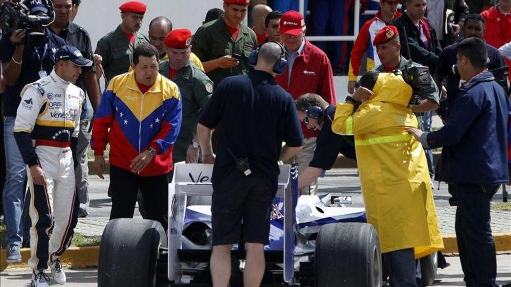 El piloto venezolano Pastor Maldonado (i), observa cómo el presidente venezolano, Hugo Chávez (2i), analiza su vehículo, antes de una exhibición al mando de un Williams en el Paseo de los Próceres de Caracas (Venezuela). EFE