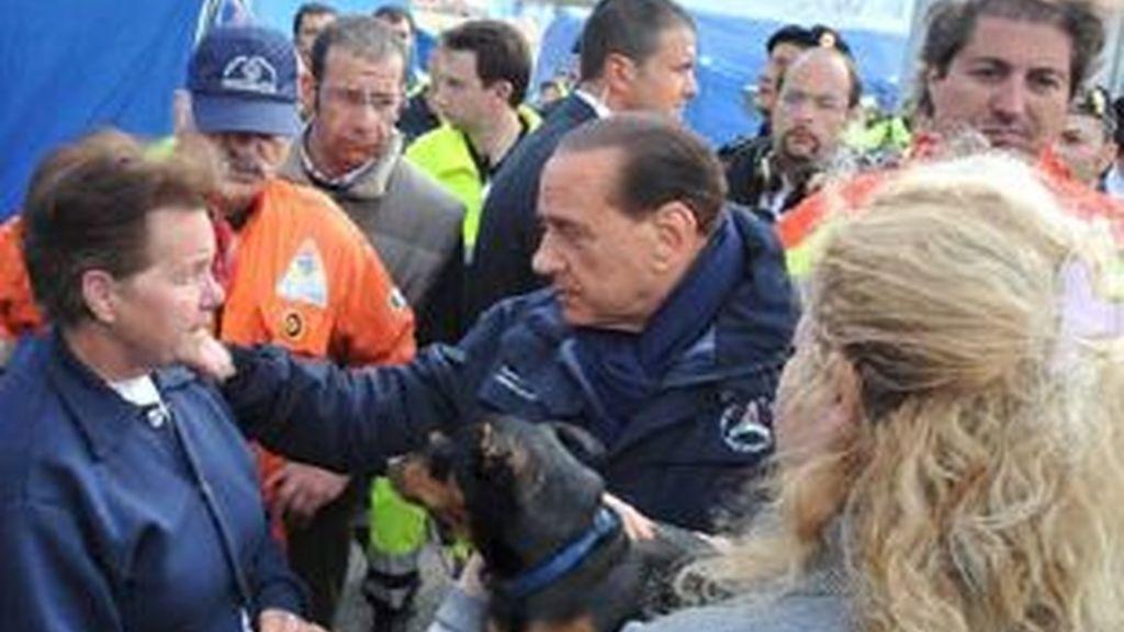 El primer ministro italiano, Silvio Berlusconi, (c), charla con una mujer víctima del terremoto, (i), en el campo de evacuados de Monticchi, cerca de L'Aquila. Foto: EFE