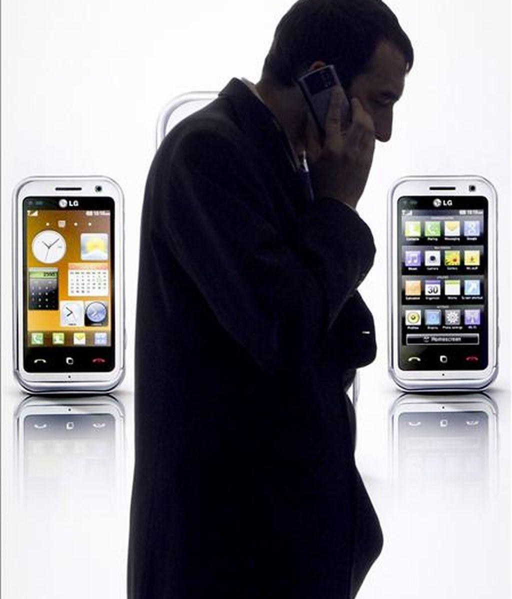 En la imagen, un visitante hace uso de su teléfono móvil ante un cartel publicitario en el GSMA Mobile World Congress. EFE/Archivo