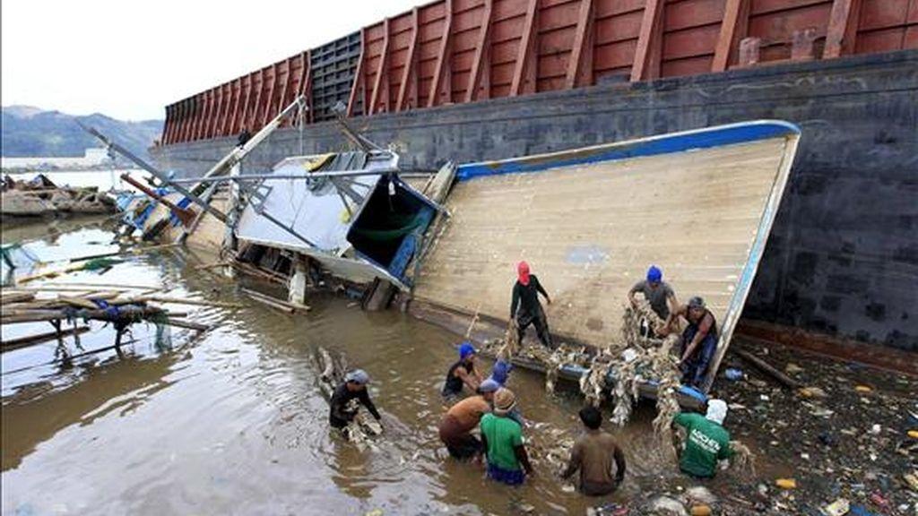 Pescadores filipinos intentan recuperar sus pertenencias de un barco de pesca dañado por el paso del tifón Consón, que ahora se dirige a Vietnam. EFE