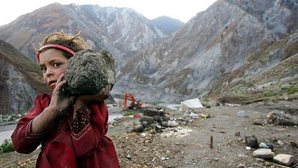 Niña refugiada ayuda a construir un muro después de un terremoto en Paquistán