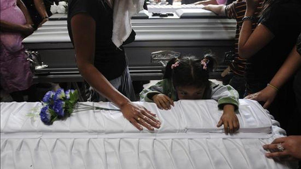 Vecinos y familiares lloran durante el funeral de tres de las siete víctimas mortales del ataque del lunes con una bomba incendiaria en contra de un autobús de transporte público en Ciudad de Guatemala. EFE