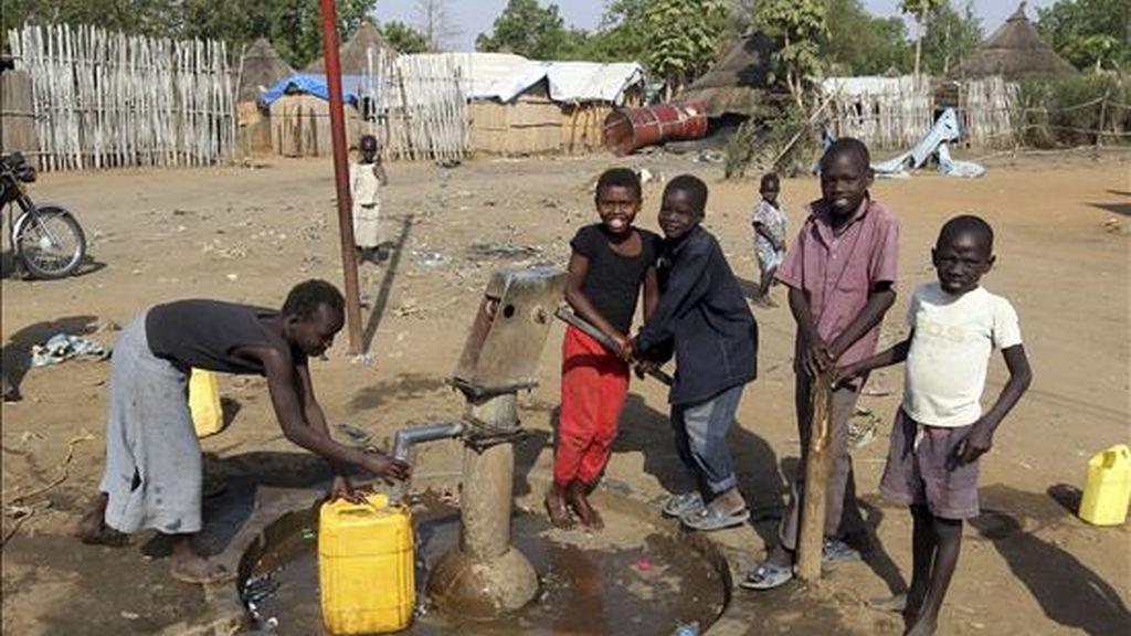 Unos niños ayuda a un hombre recoger agua en Yuba, en el sur de Sudán, hoy, 8 de enero de 2011. Dos décadas de guerra y una complicada transición culminan mañana, 9 de enero de 2011, en el Rederendum de Autodeterminación del Sur, que según todos los pronósticos, determinará el nacimiento de una nueva nación, Sudán del Sur.