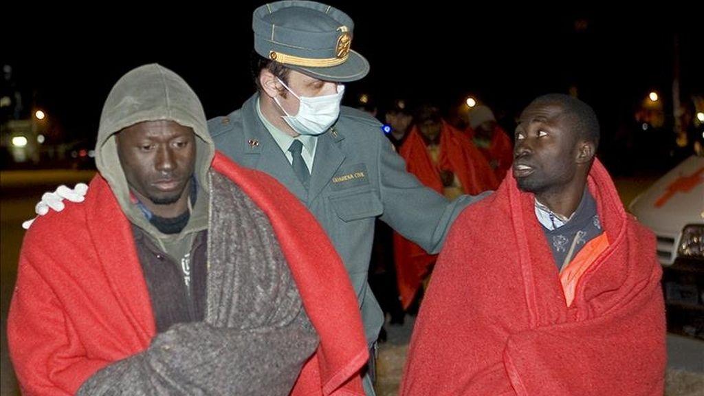 Un agente de la Guardia Civil acompaña a dos inmigrantes. EFE