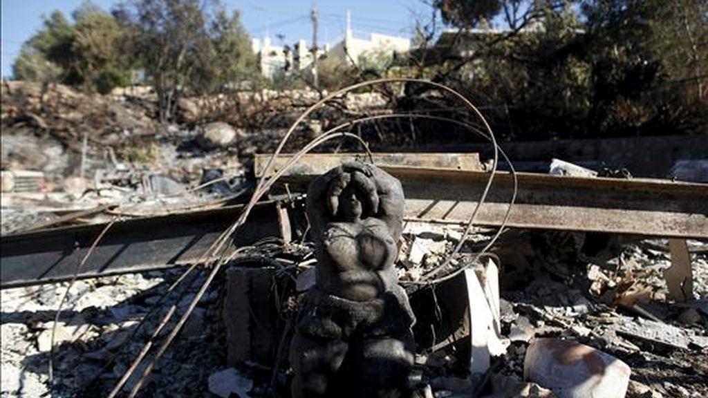 La estatua de una mujer entre los restos de una vivienda en la aldea de Ein Hod, en las afueras de Haifa, tras el mayor incendio de la historia en Israel, que sigue activo en varias áreas del norte del país, hoy. EFE