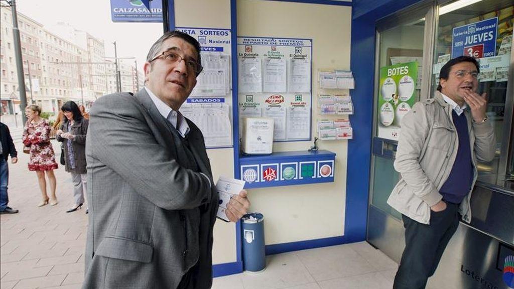 El lehendakari, Patxi López (i), se dispone a comprar lotería en una adminstración del centro de Vitoria, durante el paseo que ha dado hoy con los candidatos a la alcaldía de la ciudad, Patxi Lazcoz (d), y a diputado general, Txali Prieto. EFE