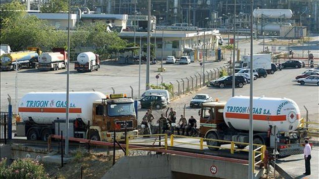 Camiones haciendo fila para llenar los tanques en una refineria a las afueras de Atenas, bajo la vigilancia de policías antidisturbios, este sábado. EFE