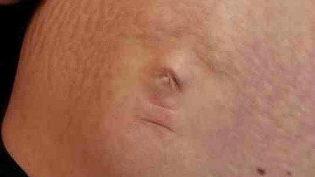 La cara del bebé a través de la barriga