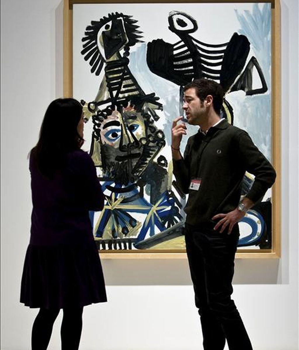 """Unos operarios observan el lienzo """"Hombre, Mujer y Niño"""", que se expone en el Museo Picasso Málaga. EFE/Archivo"""