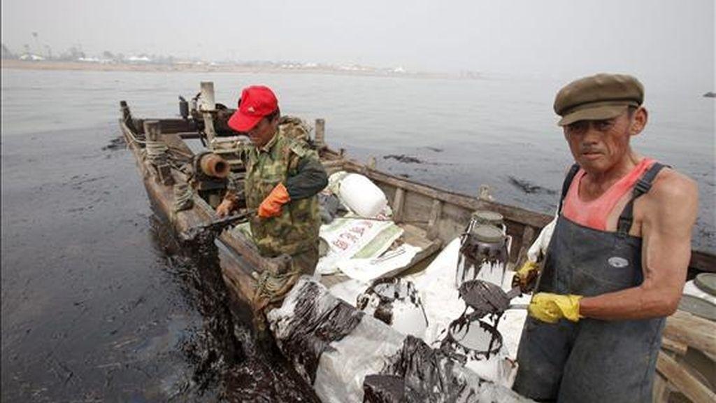 Fotografía facilitada por Greenpeace que muestra las rudimentarias tareas de limpieza del vertido de crudo, en Dalian (China). EFE
