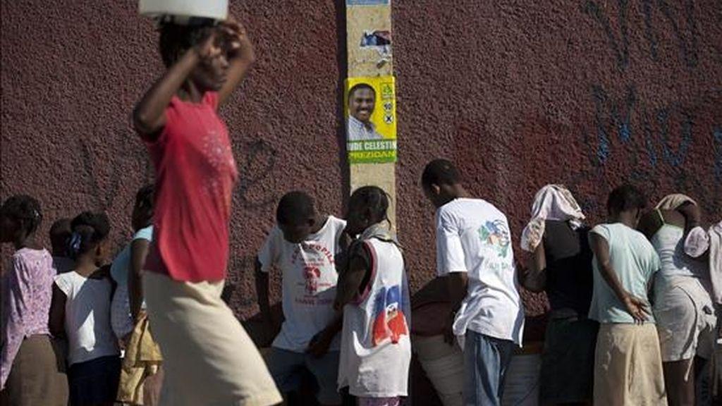 Varias personas hacen fila para recolectar agua cerca de un afiche del candidato presidencial Jude Celestin. La campaña electoral finaliza hoy en un ambiente de inquietud tras los incidentes violentos de principios de semana. EFE