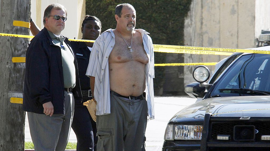 La policía con el sospechoso detenido por el tiroteo.