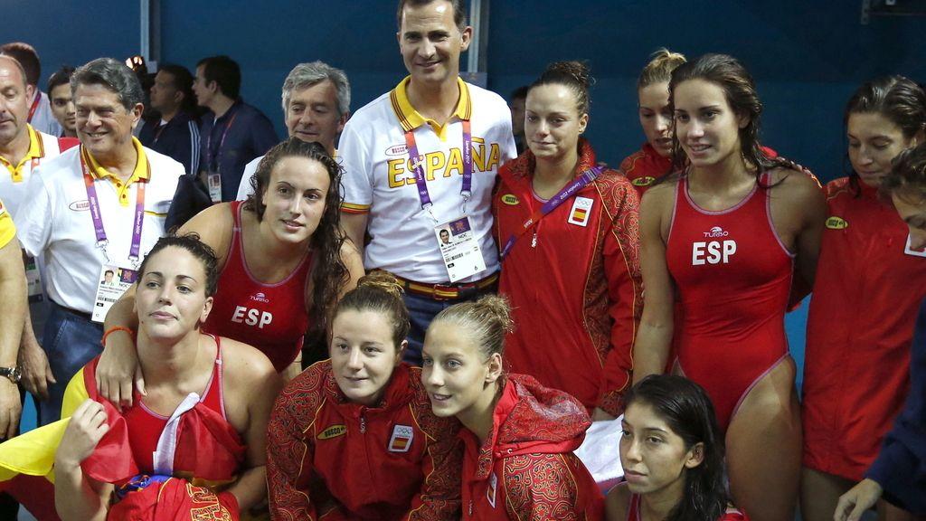 El príncipe Felipe posa con las integrantes de la selección española de waterpolo femenino, plata olímpica, tras el partido