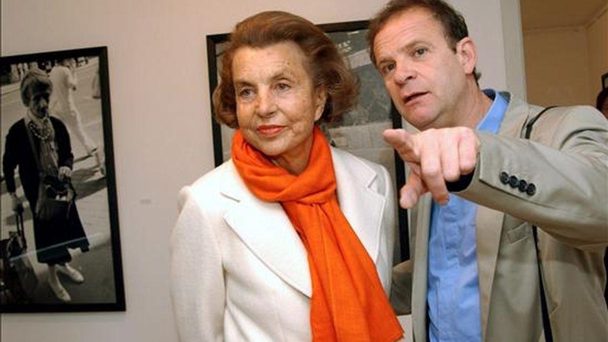 El fotógrafo francés François-Marie Banier (d) junto a la heredera de L'Oréal, la multimillonaria Liliane Bettencourt, durante su visita a una exposición de Banier en el museo Hans Lange de Krefeld, Alemania, en 2004. EFE/Archivo