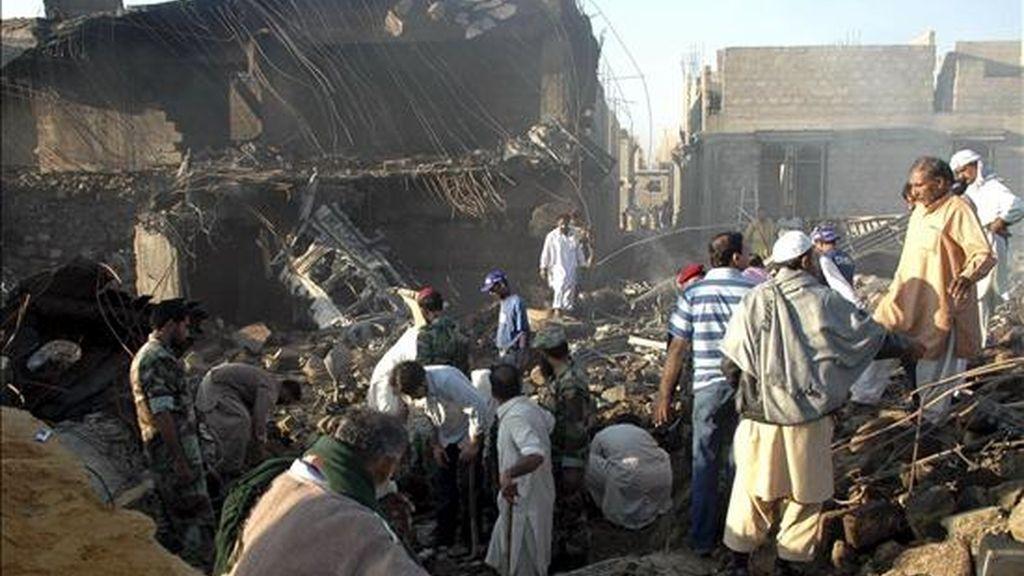Miembros de los servicios de rescate inspeccionan el escenario del accidente de un avión de carga de construcción rusa en la ciudad meridional paquistaní de Karachi (Pakistán). El aparato, un IL-76 que se dirigía a la capital de Sudán, se estrelló contra unos edificios en construcción en el barrio residencial de Dalmai de la populosa ciudad, donde están ubicadas varias instalaciones de las Fuerzas Armadas paquistaníes. EFE