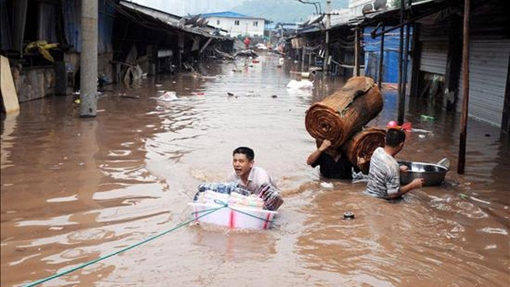 Fotografía tomada el pasado lunes,  en la que un grupo de habitantes de la ciudad de Chongqing, ubicada en el sureste de China, intenta rescatar algunas de sus pertenencias tras las inundaciones causadas por la subida del nivel de agua del río Yangtze. EFE