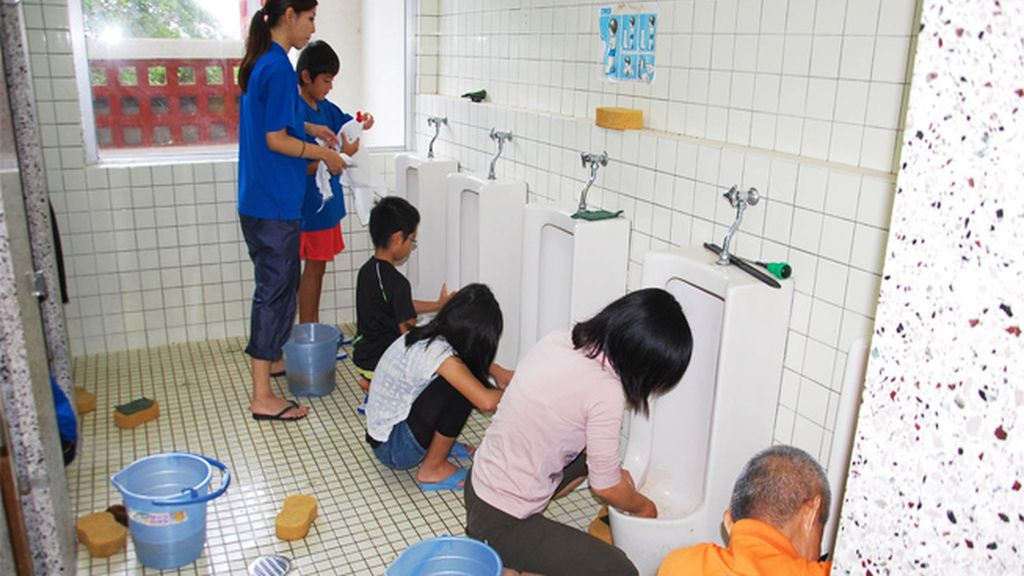 Niños japoneses limpiando los baños de su escuela