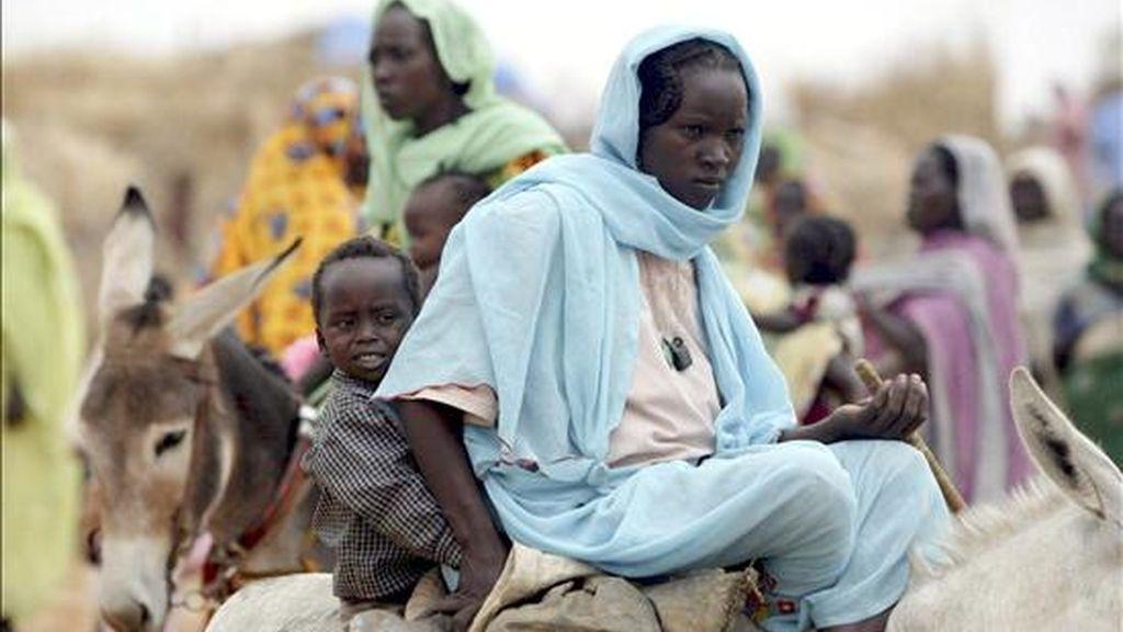 Una mujer sudanesa desplazada de la región de Darfur lleva a su hijo sobre un burro hasta el campamento de Zam-Zam, cerca de El-Fasher, Sudán. EFE/Archivo