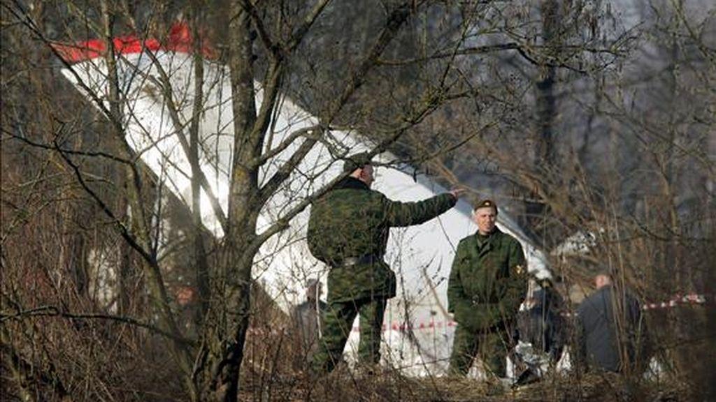 Dos oficiales de policía rusos inspeccionan hoy los restos del avión Túpolev-154 en el que viajaba el presidente polaco, Lech Kaczynski, y otras 95 personas, entre ellas más de una veintena de altos cargos políticos y militares, tras el accidente registrado ayer cerca del aeropuerto de Smolensk (Rusia). EFE