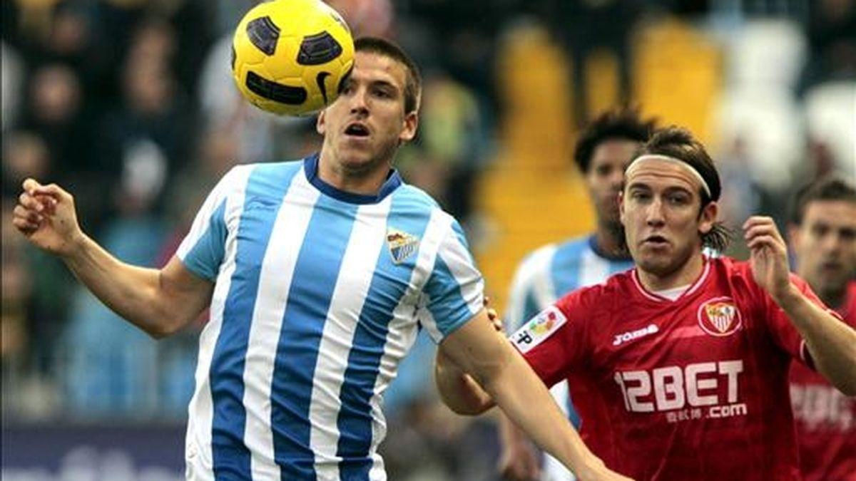 El central portugués del Málaga CF Helder Miguel Do Rosario (i) controla un balón con el extremo izquierda del Sevilla FC Diego Capel. EFE