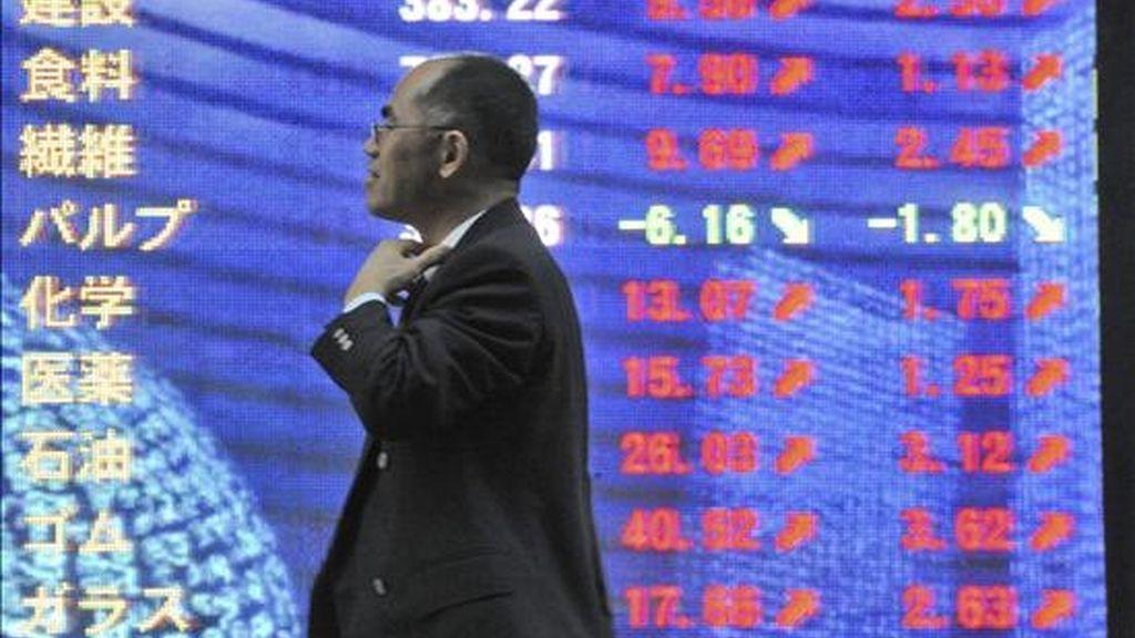 Un ejecutivo camina junto a una pantalla informativa de la bolsa en Tokio. EFE/Archivo