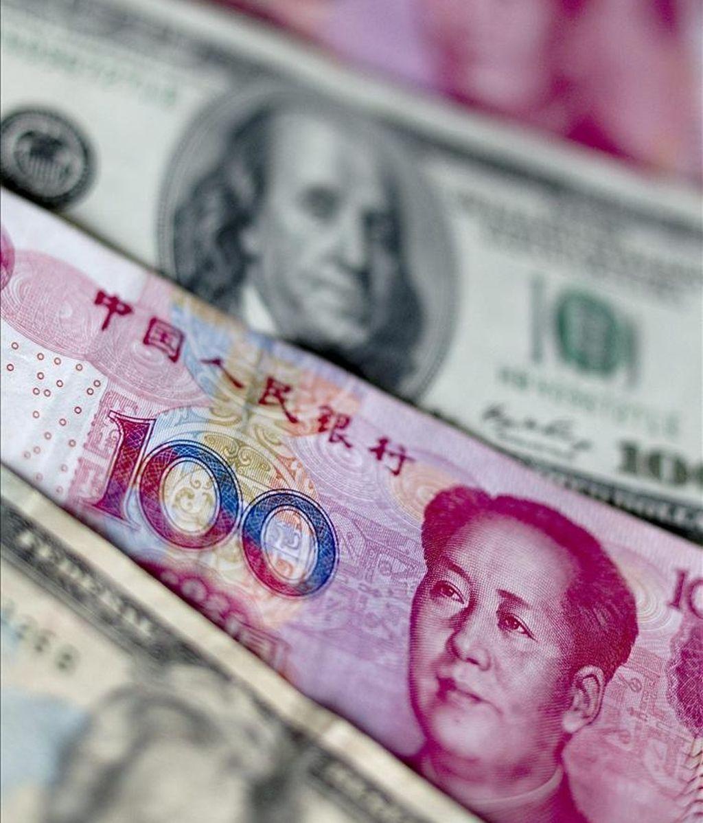 Billetes de la moneda china, el yuan y de la divisa estadounidense, el dólar, en Pekín, China. EFE/Archivo