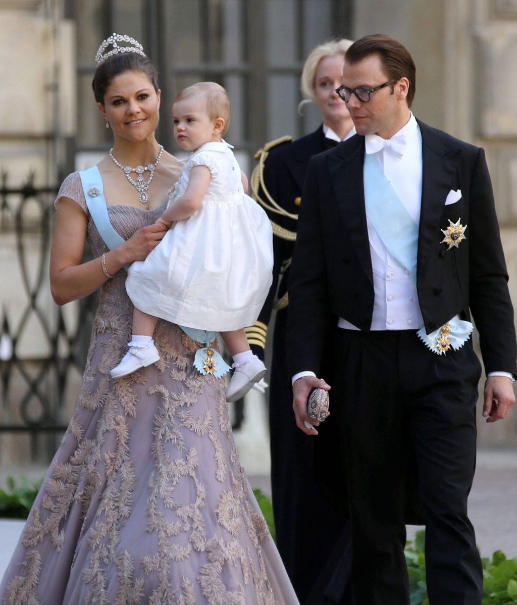 La princesa Victoria sostiene en brazos a su hija, junto al Príncipe Daniel de Suecia