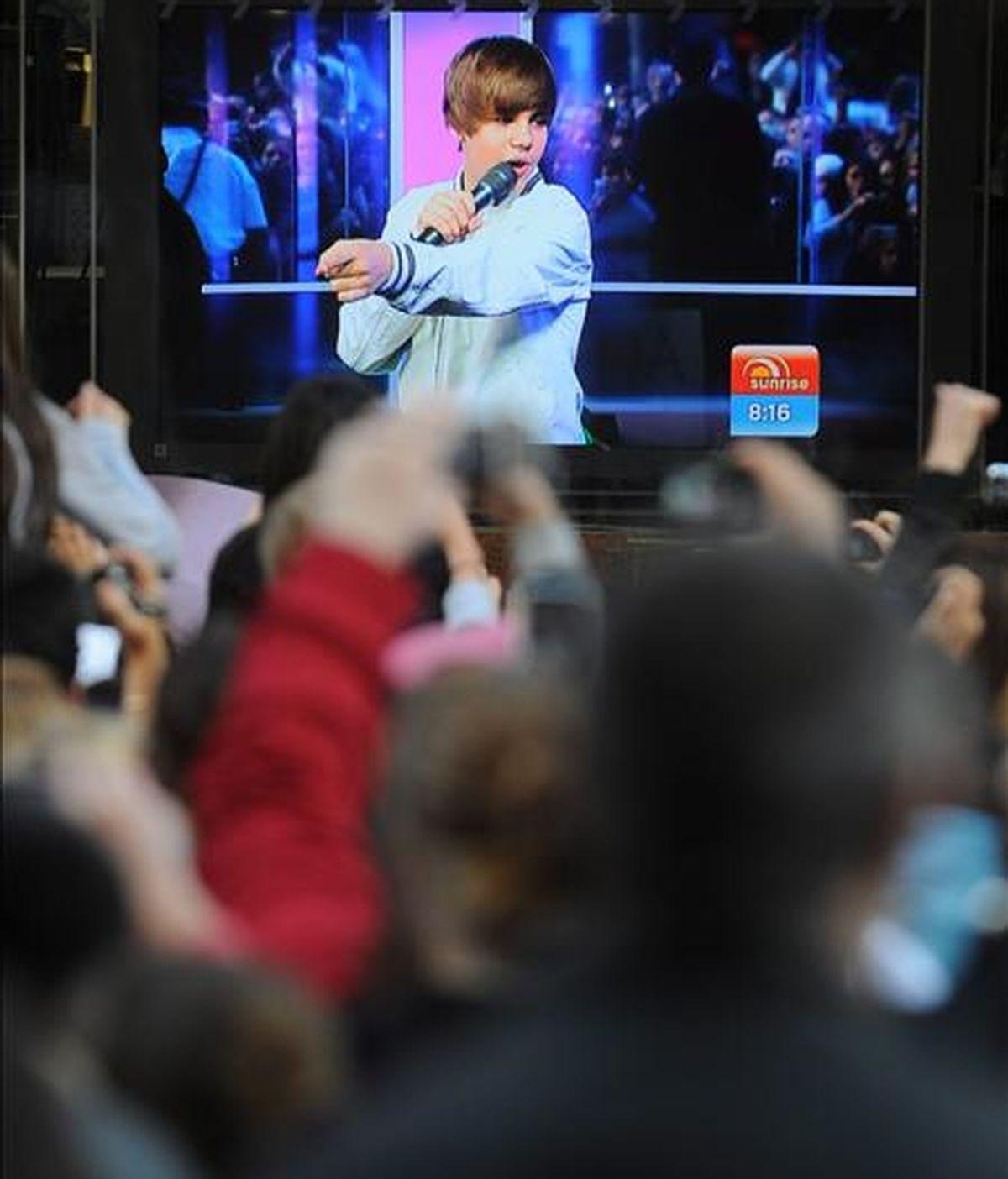 Vista de la pantalla de un televisor que muestra al cantante canadiense Justin Bieber hoy, en una entrevista, mientras cientos de fans esperan en el Martin Place, en Sidney (Australia) a las afueras de los estudios del Canal 7 para ver al artista. El concierto de Bieber and The Rocks, fue cancelado hoy por la Policía ante la avalancha de fans para asistir al concierto. EFE