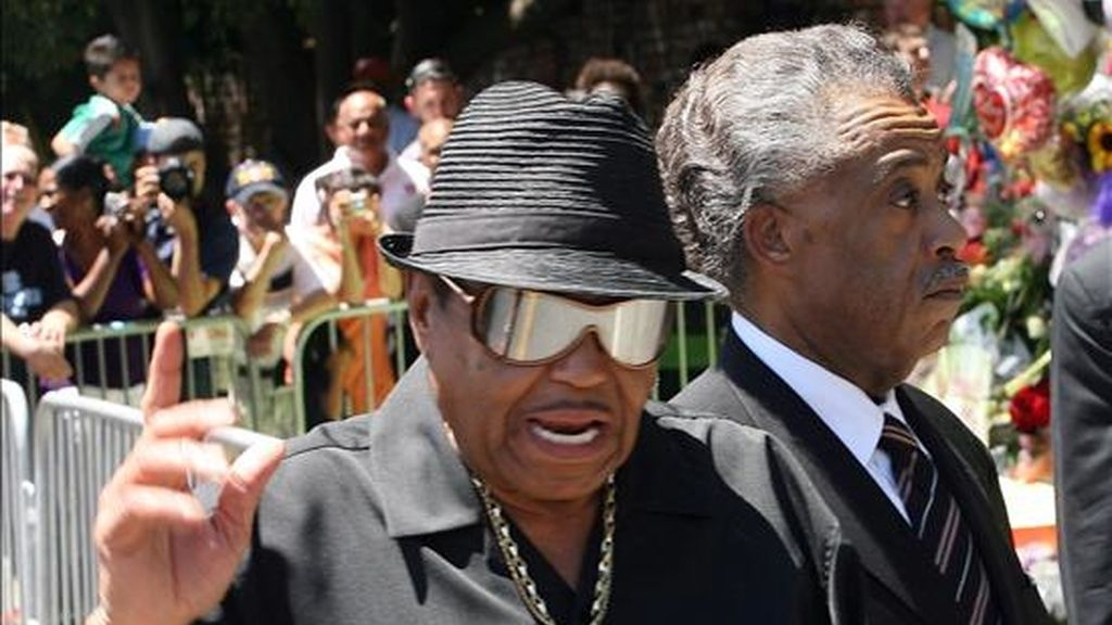 El padre de Michael Jackson, Joe Jackson, y el reverendo Al Sharpton, saludan a los seguidores del cantante después de ofrecer una rueda de prensa, en las afueras de la residencia de la familia Jackson en Los Ángeles, California (EEUU). EFE