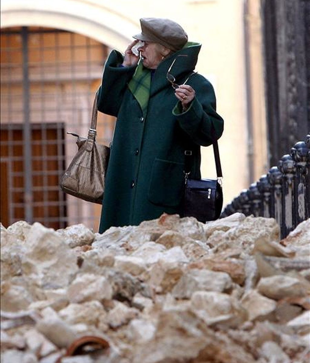 Una mujer llora junto a una pila de escombros en la ciudad italiana de L'Aquila, tras el terremoto del día 6. EFE