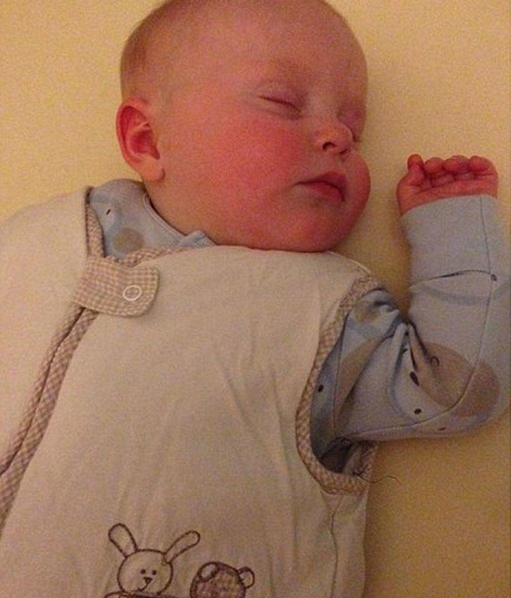 Una madre embadurna la cara de su bebé con spray autobronceador tras amamantarlo
