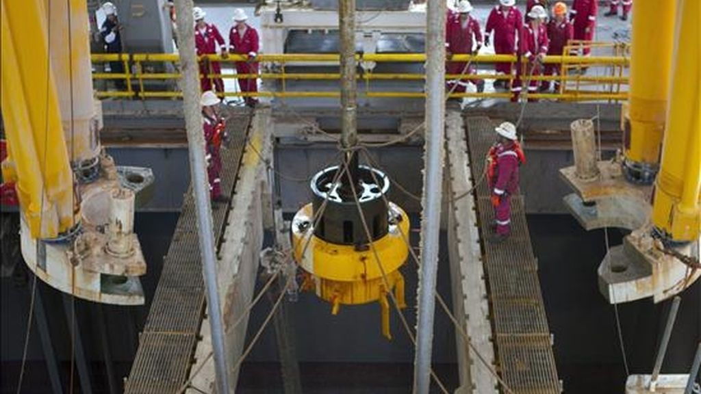 Imagen cedida este 11 de julio por BP que muestra a varios trabajadores abordo del Transocean Discoverer Inspiration mientras los robots submarinos de BP retiran la campana de contención que capturaba parte del petróleo que se escapa al Golfo de México. EFE