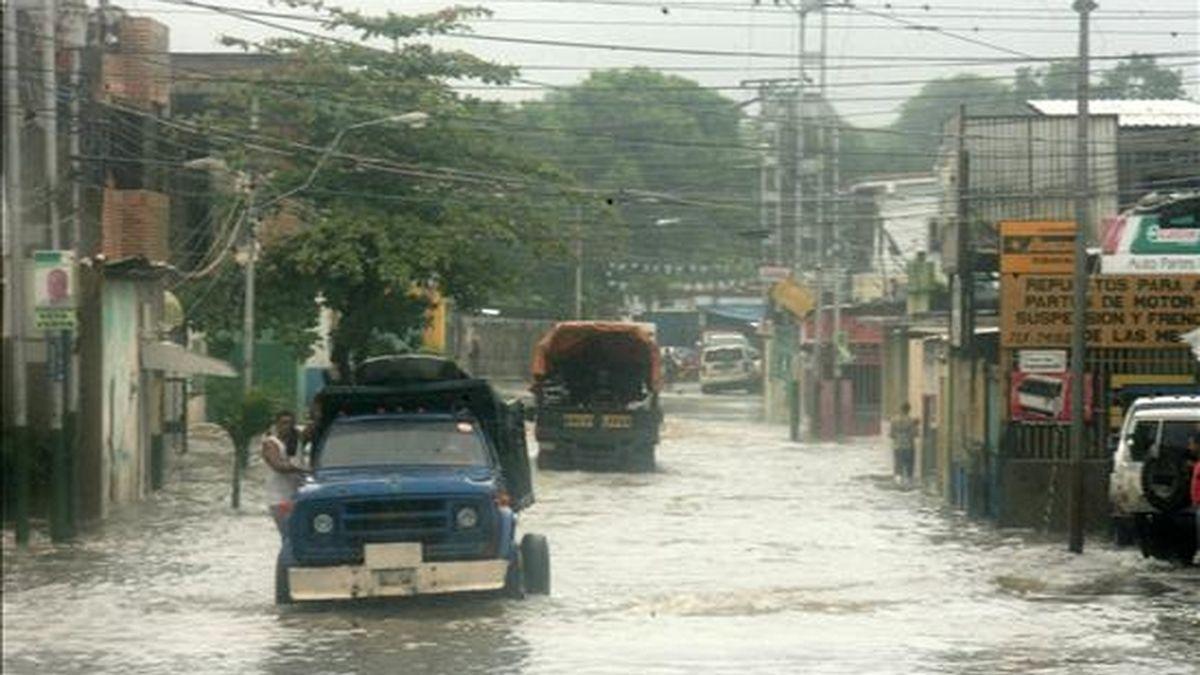 Un camión se desplaza este 3 de diciembre en una calle inundada de Río Chico (Venezuela), país donde las autoridades continúan las labores de desalojo de zonas de riesgo y despeje de vías de comunicación afectadas por los fuertes aguaceros. EFE/Archivo