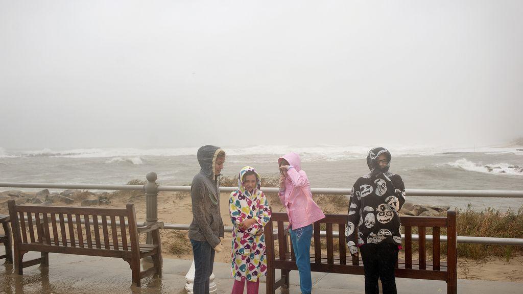 Una familia observa los efectos del huracán en un paseo marítimo