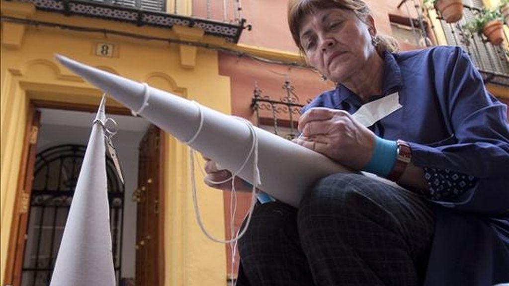 Un mujer cose capitores para los trajes de Nazareno en una calle céntrica de Sevilla con motivo de la proximidad de la Semana Santa que transformará durante siete días la capital andaluza. EFE