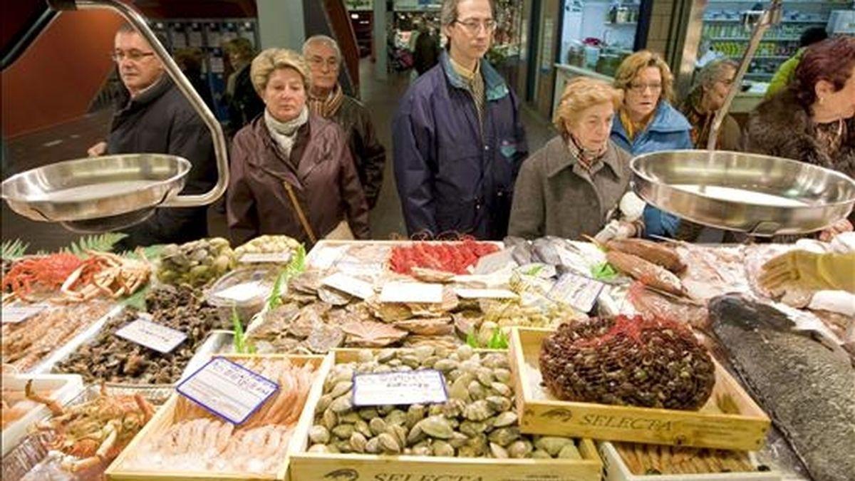 Un grupo de personas hacen cola ante una pescadería en el Mercado de Vitoria. EFE/Archivo