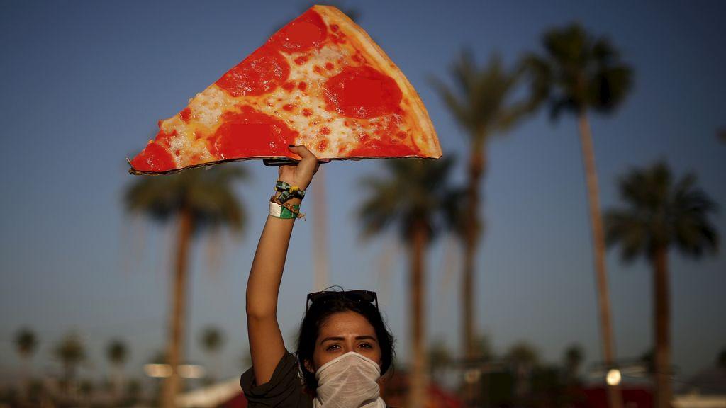 Mujer alzando una réplica de una pizza gigante