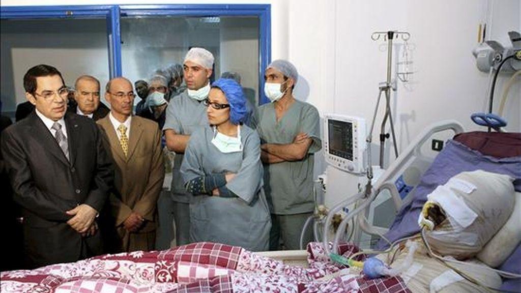 Fotografía distribuída hoy, 5 de enero de 2011, del presidente tunecino Zine El-Abidine Ben Ali (i) visitando a Mohamed Al Bouazzizi (en cama) en el hospital de Ben Arous, Túnez. Al Bouazzizi se prendió fuego el pasado 17 de diciembre, desesperado por su situación como desempleado. EFE
