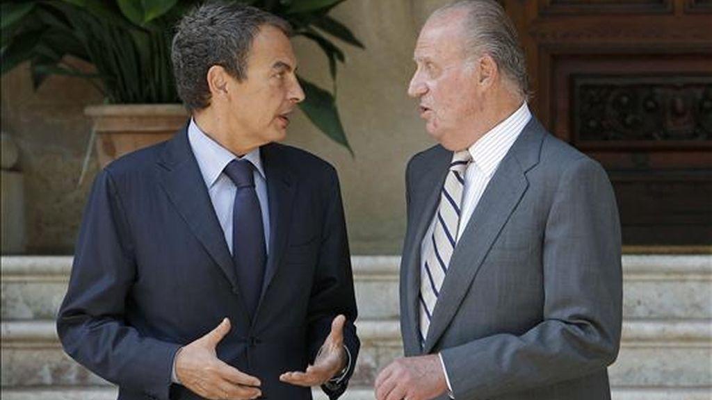 El presidente del Gobierno, José Luis Rodríguez Zapatero (i), conversa con el Rey Juan Carlos, a su llegada al Palacio de Marivent para mantener el primero de los dos despachos que celebran tradicionalmente cada año en la residencia veraniega de los Reyes. EFE