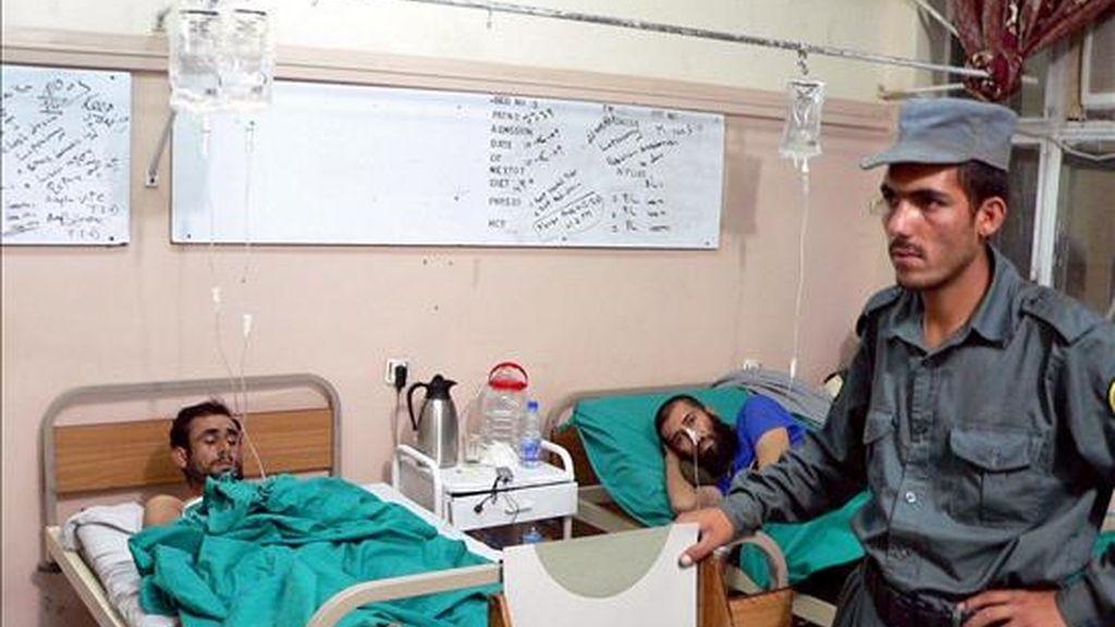 Un policía afgano vigila a dos heridos en un atentado suicida perpetrado en el distrito de Gerishk, situado en la provincia sureña de Helmand (Afganistán), en un hospital de Kandahar, hoy, 13 de junio. Ocho camioneros murieron y otras 21 personas sufrieron heridas en un ataque suicida contra un grupo de vehículos de suministro de las tropas de la OTAN en el sur de Afganistán, según informó una fuente oficial. EFE